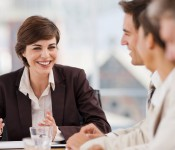 Happy businesswoman discussing with colleagues at meeting